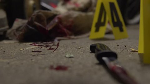 Bloody clothes and knife murder weapon detail. Part of a crime scene site at night collection. Forensic  police scientists working, looking for clues and evidence. Blood splatter analysis. In 4K.