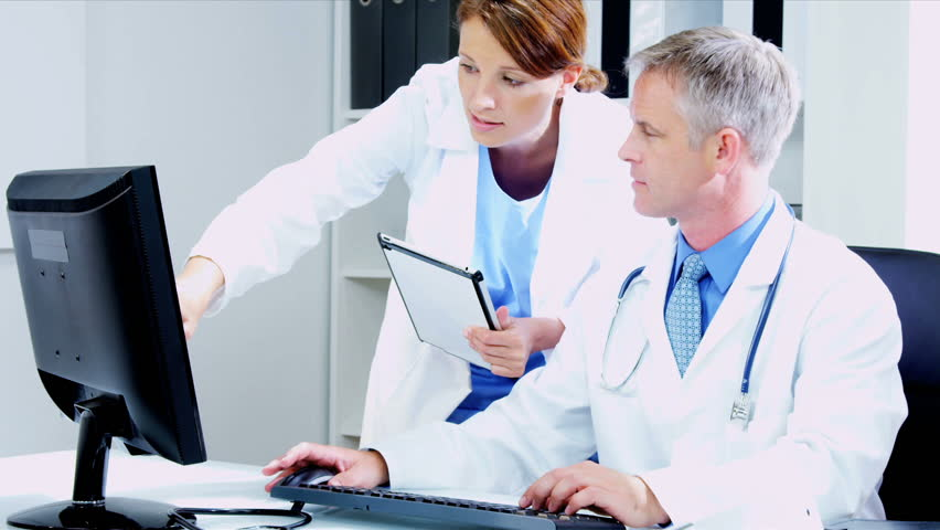 Caucasian Male medical consultant with young female doctor updating patient computer records using tablet shot on RED EPIC | Shutterstock HD Video #3294098