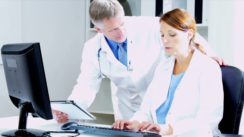 Male And Female Caucasian Medical Consultants Looking Computer