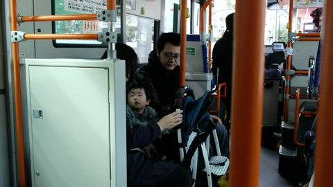 TOKYO, JAPAN - NOVEMBER 12TH, 2017. Japanese family in a public bus.