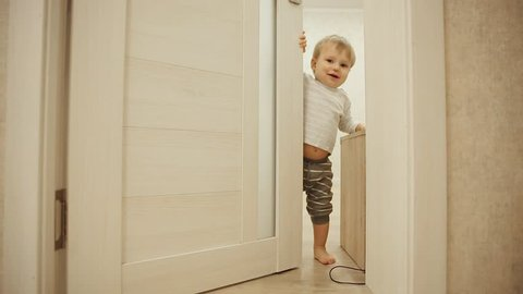 Little boy in pajamas while at home playing hide and seek with the door. Opens and closes the door to the room. Close-up.