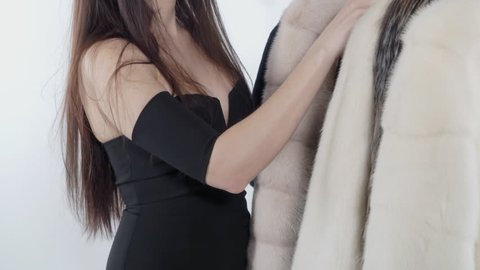 Young woman in clingy strapless dress displays her decolletage chooses a fur coat. Black, white fur mink coats hanging on hangers. Close-up.