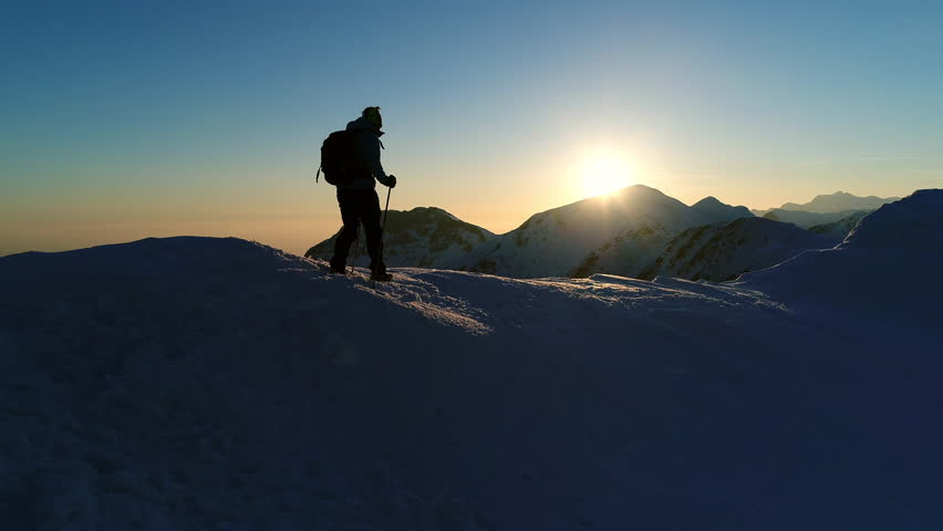 Aerial - Close up of adult male mountaineer in warm clothing hiking on snowy mountain top at beautiful winter sunset. Silhouette of man with trekking poles and a backpack walking on mountain peak | Shutterstock HD Video #32993584