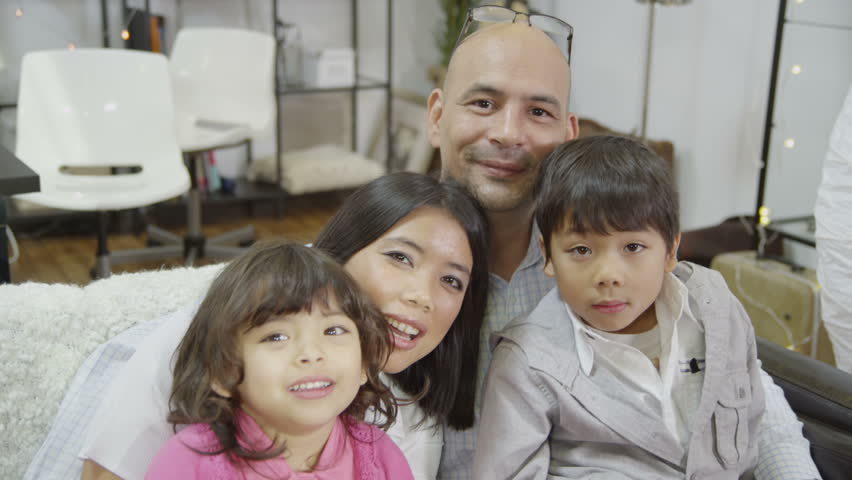 Portrait of a happy loving family that are relaxing and spending time together at home. They are looking directly into the camera and laughing. In slow motion. | Shutterstock HD Video #3299840