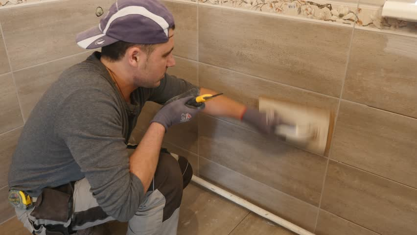 Man putting seams of beige tiles on the wall. Close up. slow motion | Shutterstock HD Video #33004564