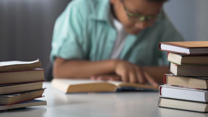 Smart Afro-American boy reading books, bookworm kid, little nerd, education