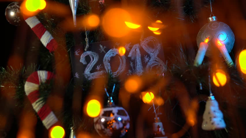 Plate numbered 2018 on a Christmas tree among toys and yellow electric lights, New Year's background. | Shutterstock HD Video #33030640
