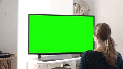 Girl Enjoying Big Green Screen Television at Home. Young woman watching green screen television at home. Shot behind model shoulders.