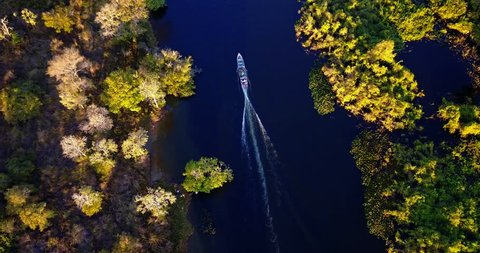 Boat sails in meanders in the river. Aerial image in the Pantanal Biome. Vegetation of riparian forest. Vertical panoramic from the top to the bottom. Mato Grosso do Sul state, Central-Western Brazil.