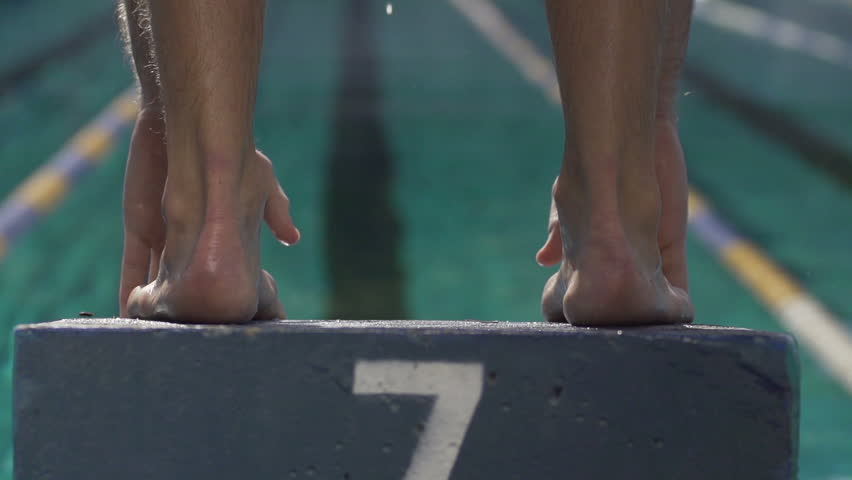 Slow-Motion Shot Of A Professional Male Swimmer Jumping Off The Starting Block