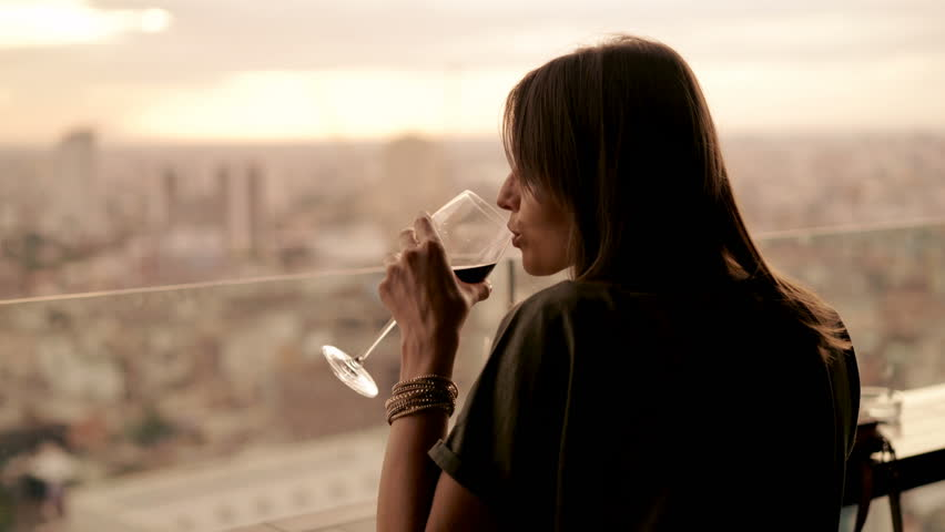 Happy woman drinking red wine while sitting in rooft bar in the city, 4K  | Shutterstock HD Video #33067414