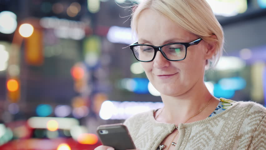 A woman uses a smarf in a big city against a background of blurred advertising lights. Popular among tourists Time Square in New York City   Shutterstock HD Video #33072451