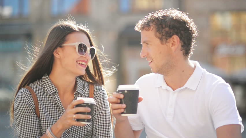 Closeup Portrait Of Lovely Couple Drinking Coffee Sitting On The Bench City Square During