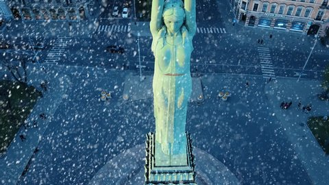 Christmas winter time in Riga Latvia in front of the statue of liberty - Milda. Snowing in Riga, Latvia. Merry Christmas
