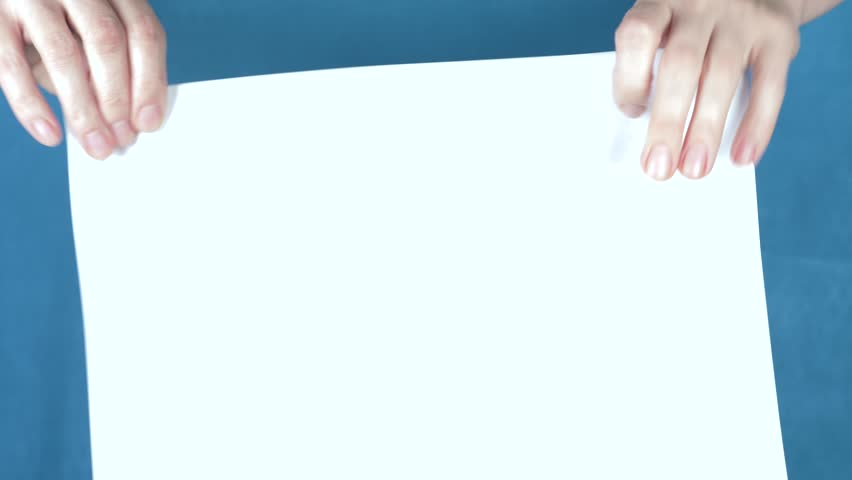 Hands tearing paper sheet, closeup on a turquoise background. 4k, slow motion   Shutterstock HD Video #33079018