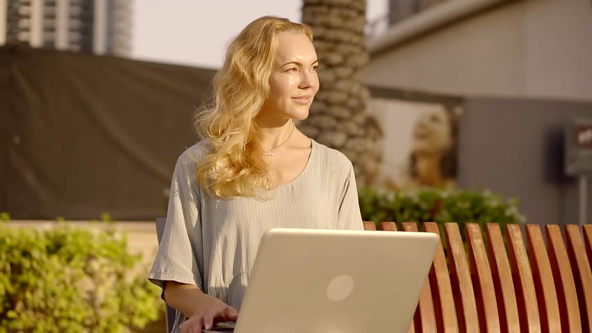 Woman is writer freelancer is sitting on a street, watching a sunset and inspiring by it, holding laptop on knees and going to type text | Shutterstock HD Video #33087214