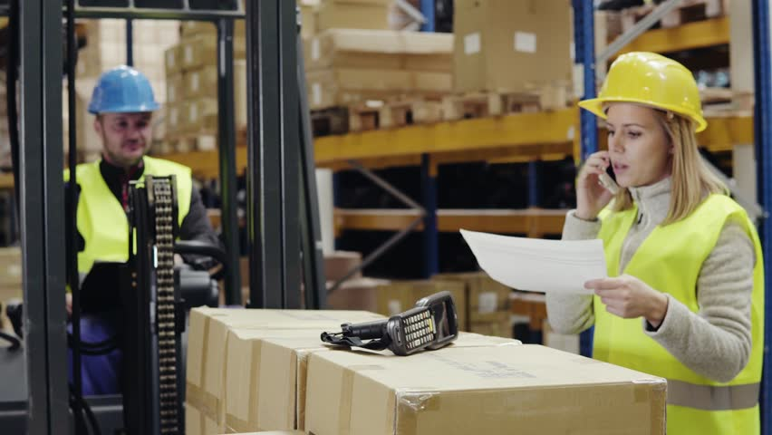 Young workers with smartphone and forklift in warehouse.