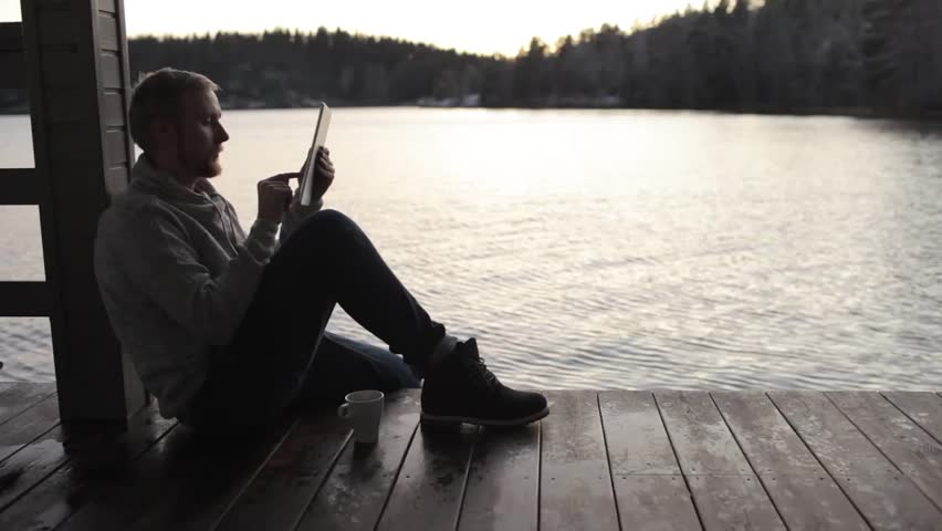Man with a tablet sits on the terrace of a house on the lake | Shutterstock HD Video #33111556