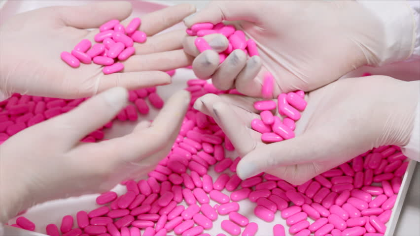 Lab technicians inspecting the quality of pills at a pharmaceutical plant.