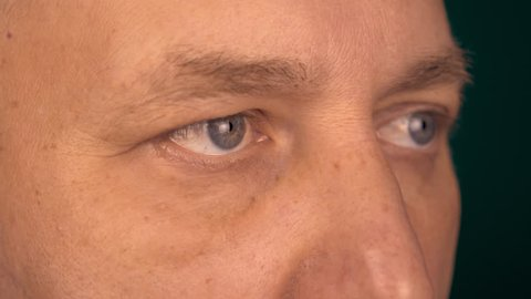 A fixed view of a man from a close distance. Male eyes look at the same point. Half-turned portrate male face extreme close up.