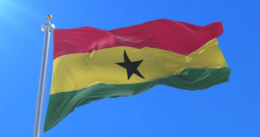 Flag of Ghana waving at wind with blue sky in slow, loop