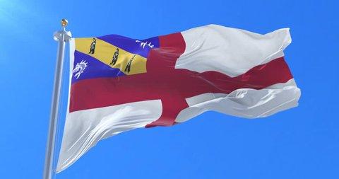 Flag of Herm waving at wind in slow in blue sky, loop