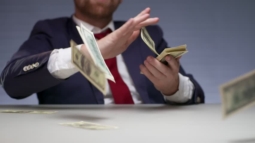 Wealthy businessman throwing bills out of a bundle money on table. Rish man holding in hands bundle dollars and spending large sums money