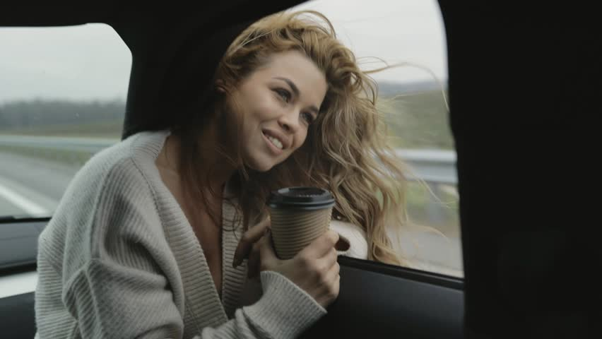 Smiling joyful pretty girl taking pleasire in her trip in the car, drinking tea coffee cacao from the cup | Shutterstock HD Video #33171424