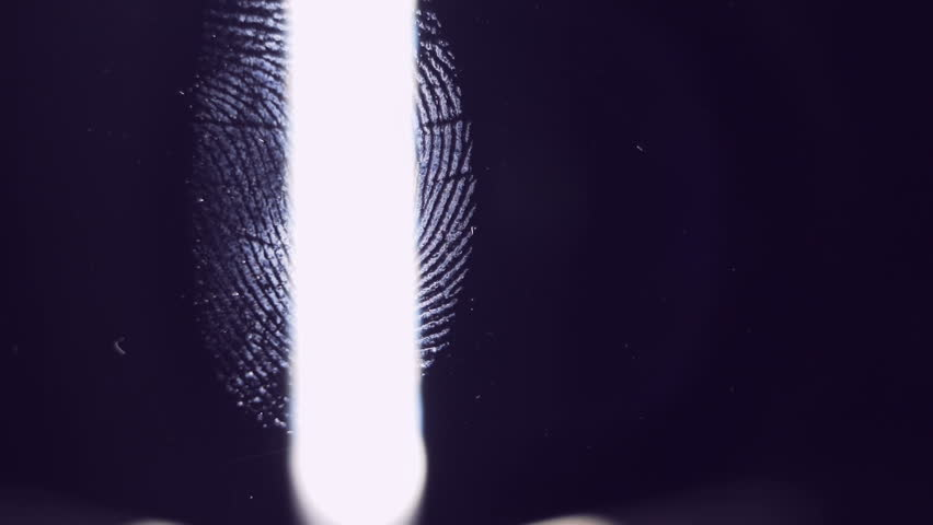 The forensic scientist examines the evidence. Fingerprints close-up. The detective uses a bright light source. #33174454