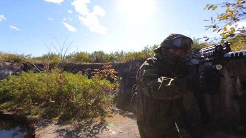 Soldier near old bunker seeking for enemy.