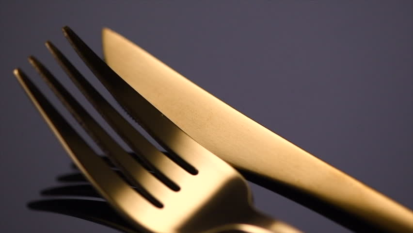 Knife and fork rotation on black background. Luxury gold Cutlery closeup. Food, Serving, Dinner concept. Table setting. Rotated 360 degrees. 4K UHD video