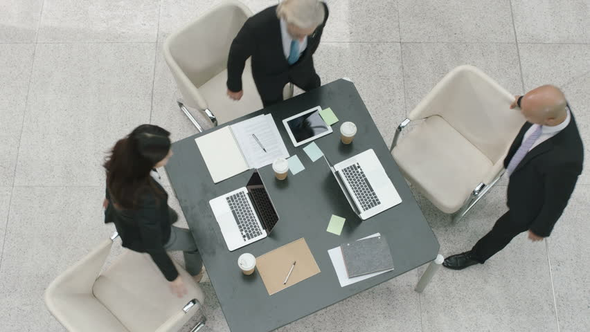 Three business people multiethnic man and woman approaching meeting table from different directions, high angle view. | Shutterstock HD Video #33213454