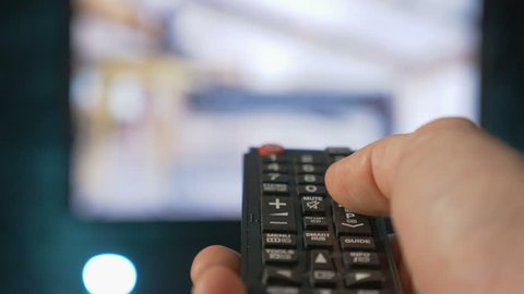 Close up mans hand holding TV remote control and changing TV channels. Blurry background