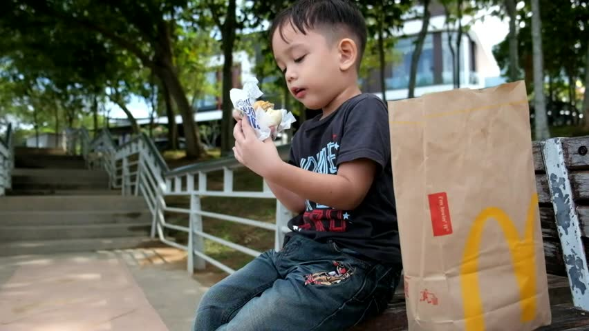 Kuala Lumpur 25 November 2017 : Close up portrait of Asian kid eating McDonald's burger at the park.   McDonald's is a fast food restaurant chain founded in 1940.