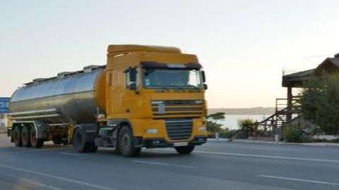 KOVLEVO, MYKOLAIV OBLAST / UKRAINE - JULY 31, 2017: Tanker truck moves on the highway near Koblevo at the sunset, Ukraine on July 31, 2017.