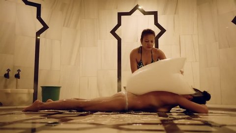 naked tanned brunette is lying on a stone table in hammam and masseur is covering her body by foam