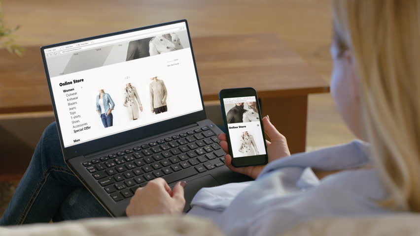 Woman Holds Smartphone and Has Laptop on Her Knees, Browses Online Store that Sales Fashionable Clothes. Shot on RED EPIC-W 8K Helium Cinema Camera.