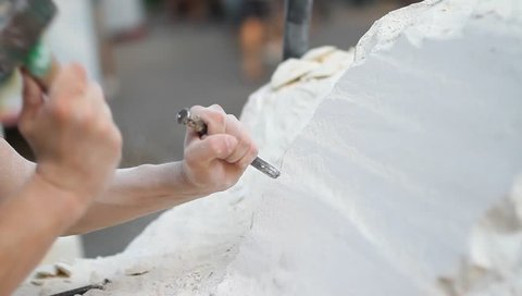Young student at work learning craftsman profession in art class, working  with hammer to carving stone statue from white stone