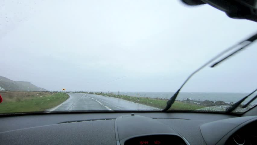 Driving in the rain on a coastal road in Scotland, UK