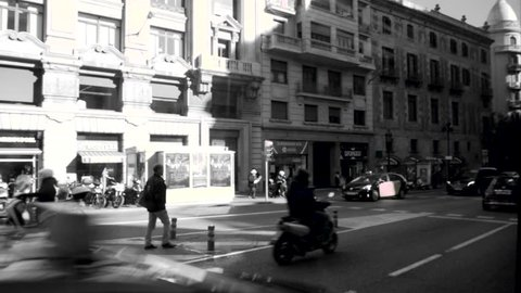 Slow motion of defocused streets of Barcelona with cars driving, locals and tourists walking on a warm summer day