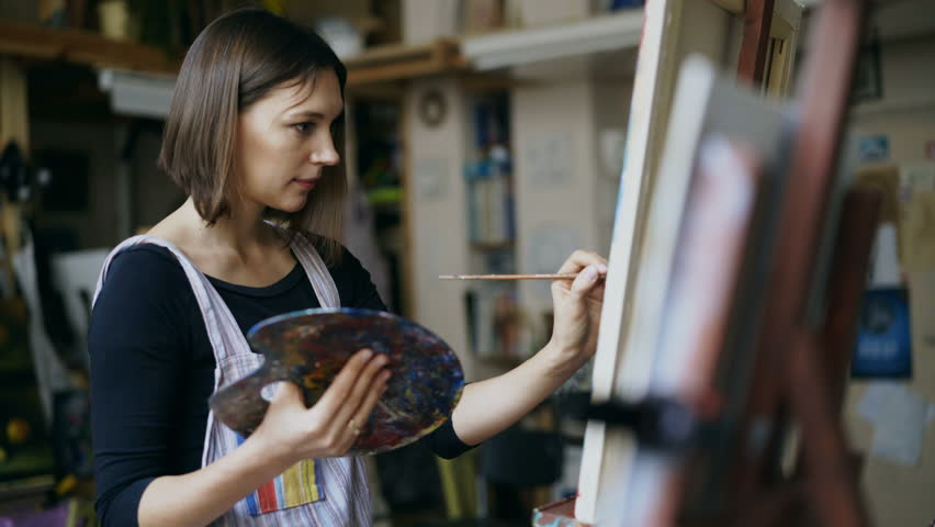 Young woman artist in apron painting picture on canvas in art studio #33281344