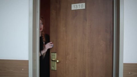 A young girl looks in different directions from the hotel room door, and then something frightened and quickly slams the door.