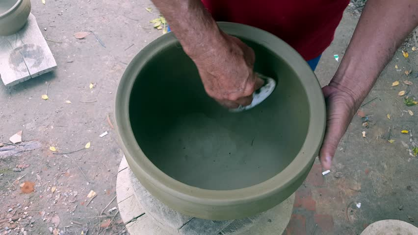 closeup man hands polish large finished clay pot inner side at making earthenware crockery process