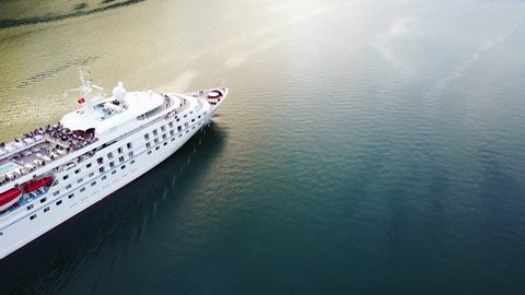 Aerial view of luxury cruise ship sailing from port on sunrise through the bay