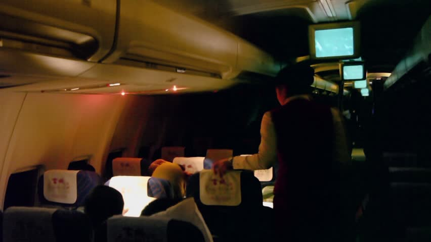 URUMCHI - NOV 28: Stewardess switches light in dark cabin of aircraft with passengers on Nov 28, 2011, in Urumchi, China.