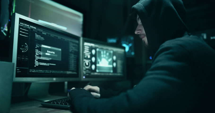 Dangerous Hooded Hacker Breaks into Government Data Servers and Infects Their System with a Virus. His Hideout Place has Dark Atmosphere, Multiple Displays, Cables Everywhere. | Shutterstock HD Video #33305584