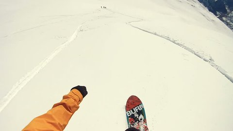 Point of view shot of Actionsportlers snowboarder while freeride in remote area in Europe Alpes