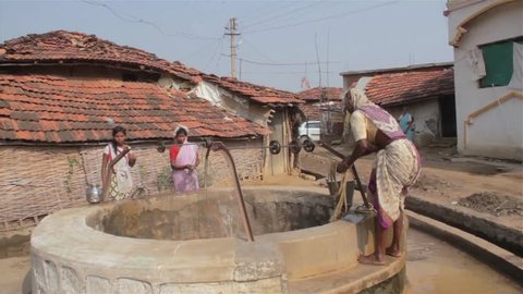 A traditional Village lady pulling water out of the water well in rural India