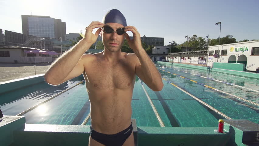 Slow Motion Of Muscular Built Swimmer Putting On Swimming Goggles.