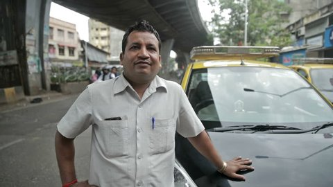 A proud and smiling taxi driver standing in front of his taxi while vehicles passing in the background. Real people of India
